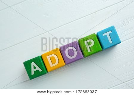 Colorful cubes with word ADOPT on wooden background