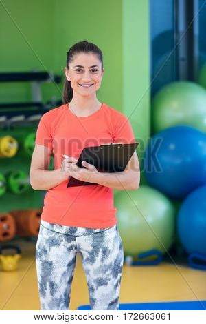 Portrait of smiling female fitness instructor writing in clipboard while standing in gym.
