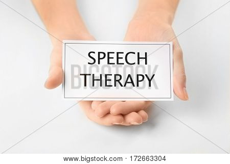 Speech therapy concept. Hands holding card on white background