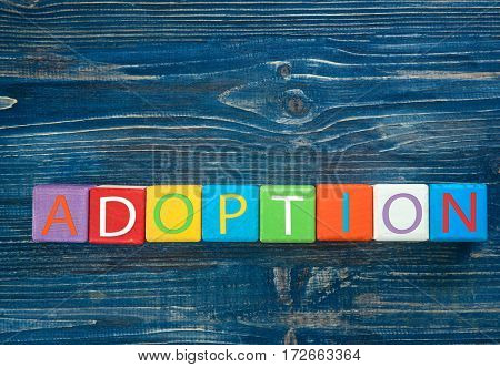 Colorful cubes with word ADOPTION on blue wooden background