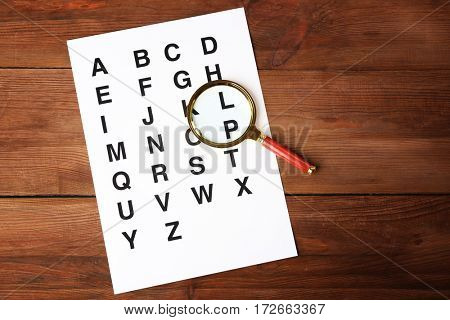 Paper with alphabet and magnifier on wooden background
