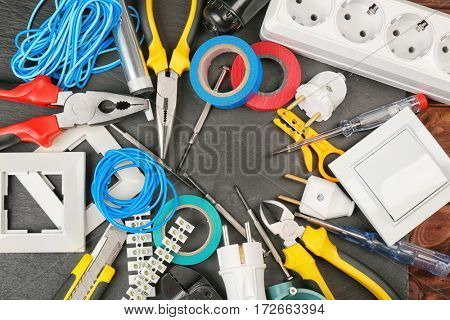 Different electrician tools on dark background