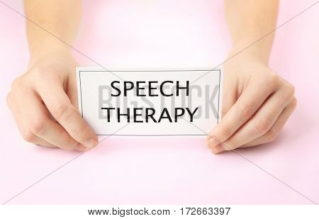 Speech therapy concept. Hands holding card on light background