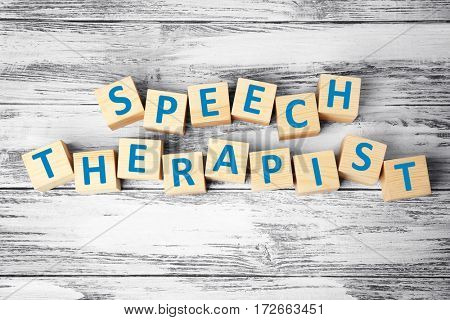 Cubes with text SPEECH THERAPIST on wooden background