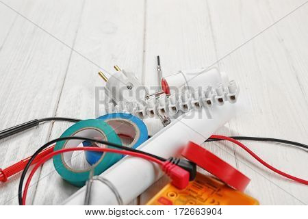 Electrician tools on white wooden background