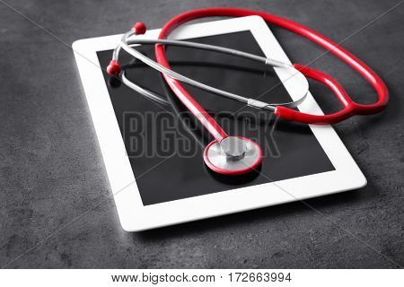 Stethoscope and tablet pc on grey table