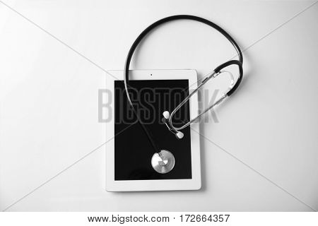 Stethoscope and tablet pc on white background