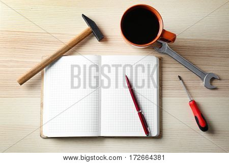 Notebook and repairing tools with cup of coffee on wooden background
