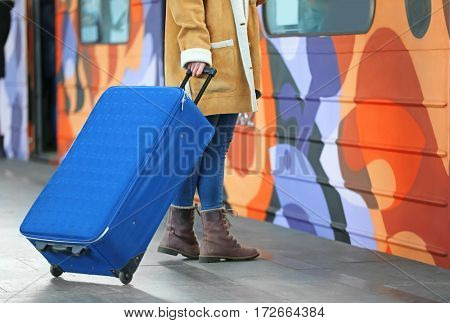 Woman at the railway station with   suitcase
