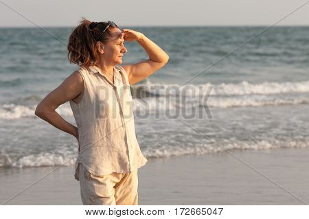 Portrait of senior woman standing on the beach. She closes his hand over his eyes from the sun.
