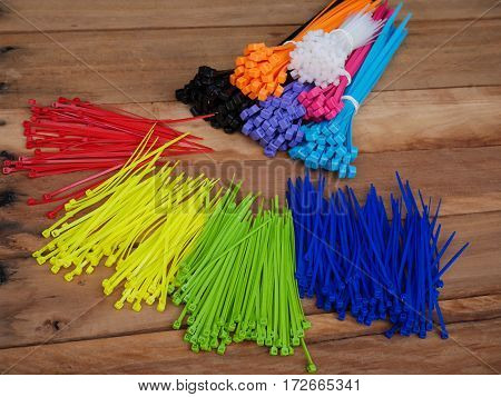 Self-locking plastic tying cables on wooden background and close-up colorful cable ties selective focus.