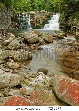 Double waterfall and stream in a wooded mountain valley.