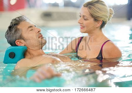 Man in spa pool doing exercises with physical therapist