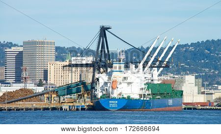 Oakland CA - February 12 2017: Bulk carrier DOGAN loading at Schnitzer Steel at the Port of Oakland. Schnitzer Steel recycles scrap metal into finished steel products such as rebar and wire rod.