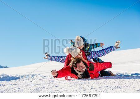 Ski, snow sun and fun - happy family on ski holiday.