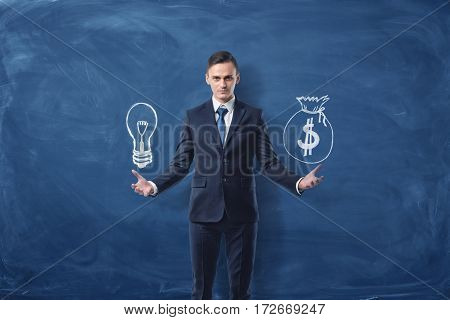 Businessman holds a lightbulb in one hand and a bag of money in another hand on blue chalkboard background. Innovation. Ideas for business. Development and profit