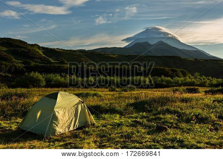 Tourist tent on a background of the Vilyuchinsky stratovolcano at dawn. View from the brookvalley Spokoyny at the foot of outer north-eastern slope of caldera volcano Gorely.