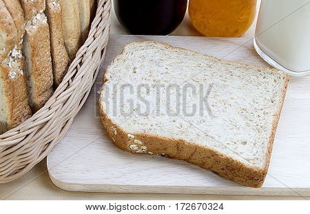 cut bread on cutting wooden board with milk and jam