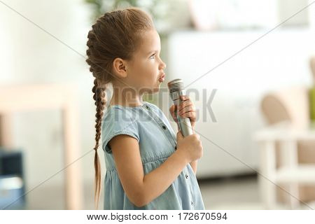 Cute little girl with microphone at home