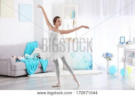 Young beautiful ballerina dancing in room