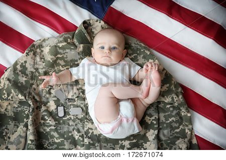 Cute baby on military clothing and flag