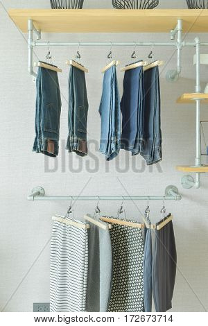 Skirts And Jeans Hanging In Industrial Style Walk In Closet