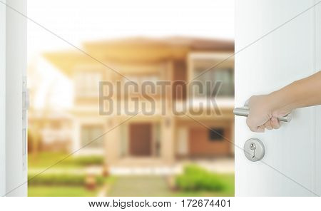 Man Hand Opening White Door To Modern Home Exterior As Background
