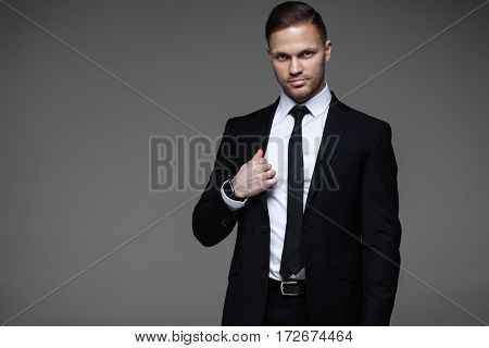Young handsome businessman in black suit on gray background