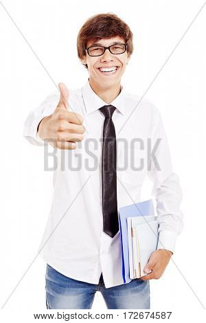 Young man wearing glasses, blue jeans, white shirt and black tie, holding books and folders in his hand, smiling and showing thumb up isolated on white background - students and education concept