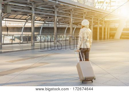 Businesswoman traveler with luggage at city background