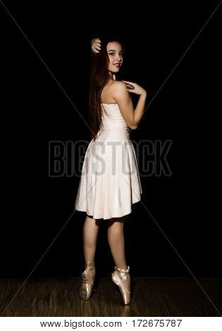 Young ballerina with a perfect body is dancing in pointe shoes on a dark background.