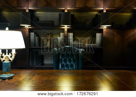 Private office.Spacious dark wood home office in classical style with large table and vintage armchair.