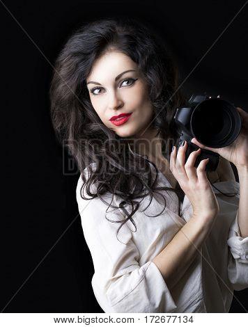 Happy brunette photographer woman holding camera over dark background