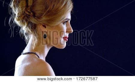Woman in little black cocktail dress with bare shoulders on black background. Female portrait in profile with evening make-up, hairstyle and jewelry.
