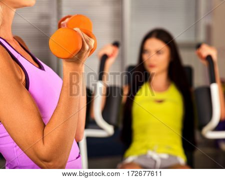 Friends gym workout. In fitness center woman working. Slim girl sitting on sport equipment and do exercises on background. Female biceps in the foreground. How to get body you want.