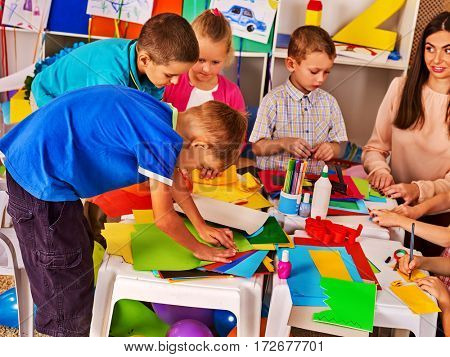 Children cutting paper in class. Kids development and social lerning children in school. Children's project in kindergarten. Low tables for work and creativity. Group girl , boy with teacher together.
