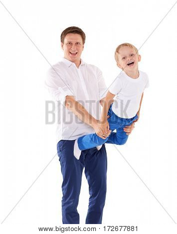 Young father with child are doing gymnastic exercises, holding son in hands on a white background. Healthy lifestyle.