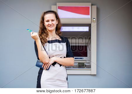 Young happy brunette woman withdrawing money from credit card at ATM