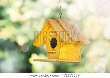 yellow wooden birdhouse in the garden. springtime easter sunlight . spring concept