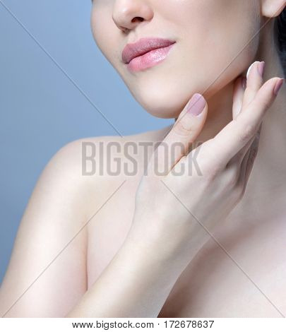 beauty closeup portrait of attractive young caucasian woman brunette on blue background studio shot skincare face skin applying cream hands neck. fresh looking perfect skin