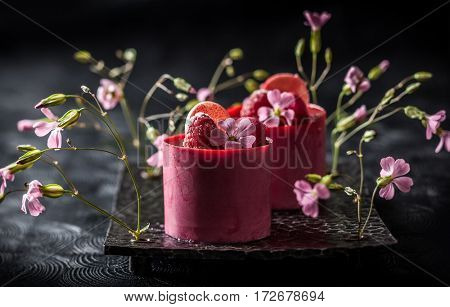 Raspberry mousse cakes with fresh berries and macaroni. Soft focus