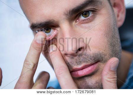 Man applying contact lens in ophthalmology clinic