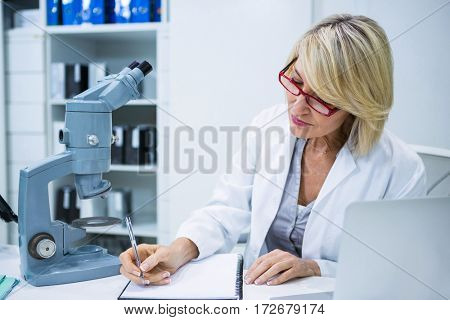 Optometrist writing in file at ophthalmology clinic