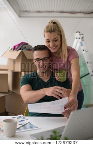 Young couple moving in a new home. Man and woman at the table using notebook laptop computer and plans with boxes around them