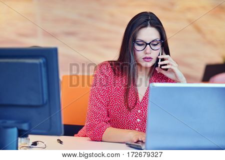 Women talking on phone. Successful business woman working at the office.