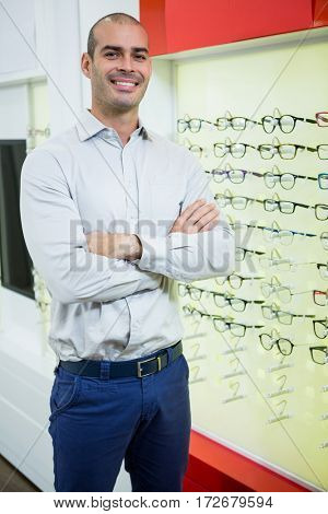 Portrait of smiling male optician standing with arms crossed in optical store