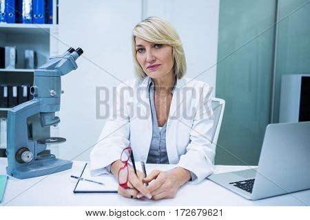 Portrait of optometrist sitting in ophthalmology clinic