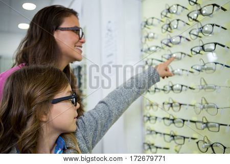 Mother and daughter selecting spectacles from display in optical store