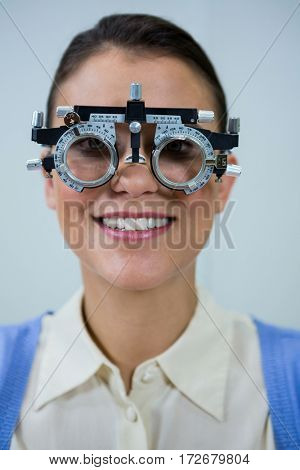Smiling female patient wearing messbrille during eye examination in in ophthalmology clinic