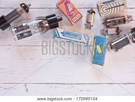 Close up picture with different tipes of electronic radio lamps and packaging them on white shabby wooden background.